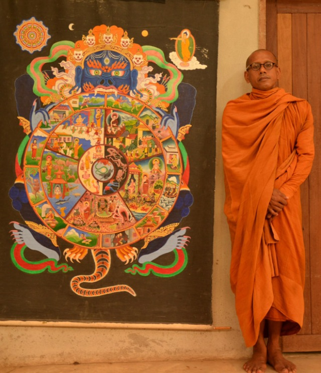 Ven. Ajāhn Mehdī, the Abbott of International Dharma Hermitage (Sumedhaso Donkiem), in front of a painting representing Paticcasamuppada.